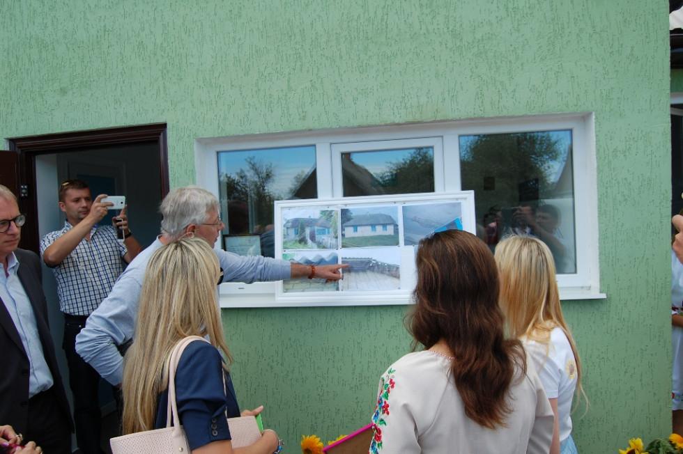 Ніл Вокер, координатор системи ООН в Україні, оглядає порівняльні фото приміщення до реконструкції і після